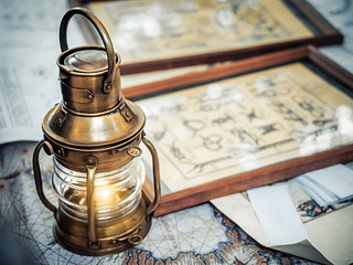 Foto auf AluDibond Schiff Old brassy ship lantern stands on a map of the seas near pictures with the image of sea knots