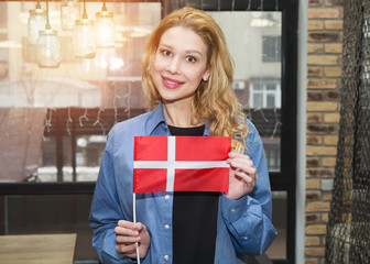Young blond woman with Denmark flag on the background of the company office. Studying abroad.