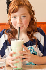 Portrait of redhead girl drinking milkshake in restaurant