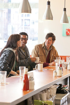 Happy customers multiethnic group of people friends having fun drinking coffee together in cafe diner