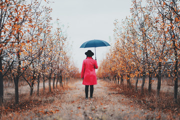 Woman in red coat and with umbrella between trees in apple garden at autumn season. Minimalism, travel, nature concept.