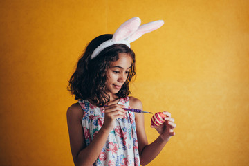 A happy girl painting Easter eggs over color background
