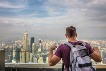 Fototapete - Tourist with a backpack enjoys the panoramic view of the Kuala Lumpur skyline