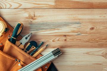 Carpentry tool belt on woodwork workshop desk, top view
