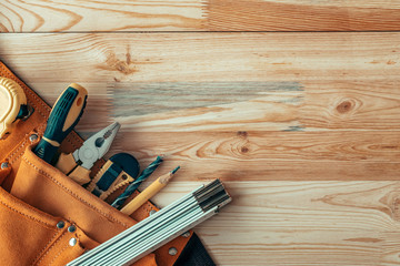 Obraz Carpentry tool belt on woodwork workshop desk, top view - fototapety do salonu