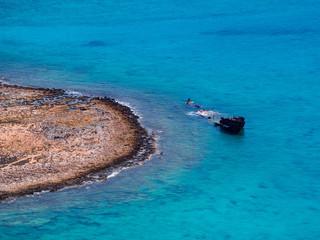Sunken ship in beautiful blue waters of tropical island
