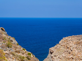 View of endless blue sea, two rocky hills meet in the foregorund