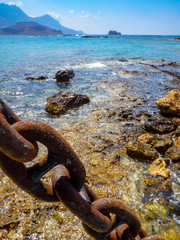 Big rusty ship chain, shallow blue water and rocky coastline