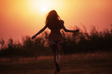 Beautiful redhead girl silhouette in a pink dress against a background dawn. Girl run towards sunrise. Misty morning dawn over the field. Yellow summer sunrise. Bright morning sun. Female silhouette