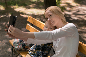 mother and son take selfie on a bench in the park in summer
