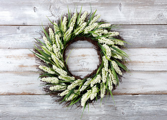 Natural flower wreath on white weathered wooden background