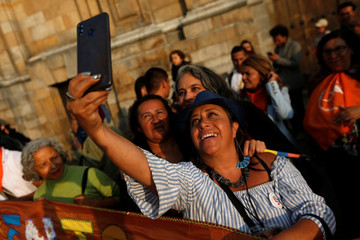 A woman takes a picture with a cell phone during a protest in support of the Special Jurisdiction for Peace (JEP), in Bogota