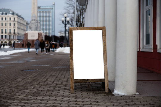 Blank ad space on a wooden stand in the street outside