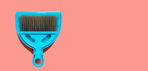 A pale blue dustpan and brush lying on living coral background. In the style of pop art. Top view.
