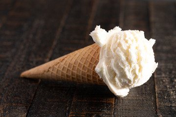 Fototapete - A Scoop of Vanilla Ice Cream on a Wooden Table