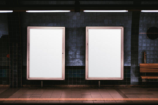 Two empty ad vertical posters templates on a metro platform; blank information banners placeholders indoors; a subway or a train station with two white billboards in front of a blue tile wall