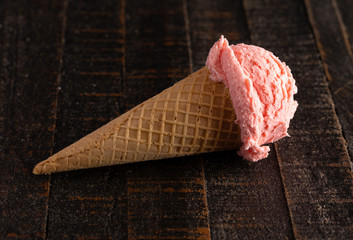 Fototapete - Scoop of Strawberry Ice Cream Laying on a Wooden Table