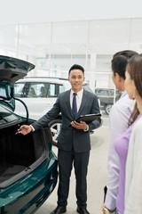 Salesman showing car trunk
