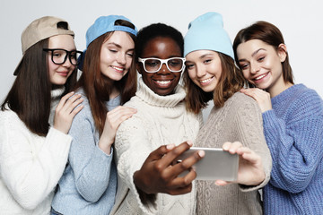 five different nation girls dressed in casual wear make selfie