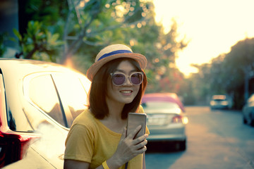 asian woman by traveller lifestyle with smartphone in hand toothy smiling face relaxing emotion in citylife