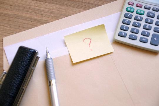 茶封筒に入った書類とはてなマークの書かれたメモと印鑑とペンと電卓