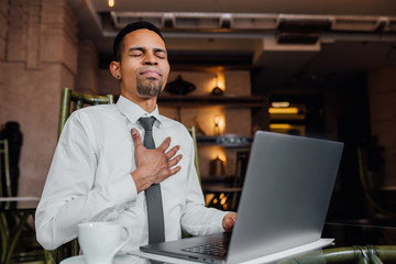 black man happy in front of laptop, hands on chest, in a white shirt, indoor,