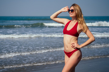 Happy woman smiling and having fun at beach. Summer portrait of young beautiful girl in red bikini
