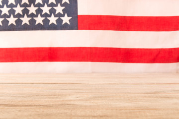 Wooden table and American flag in the background. Selective focus.