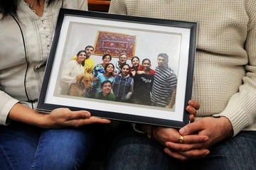 Manant and Hiral Vaidya pose with a photograph showing six members of their family who were killed in the Ethiopia Airlines crash