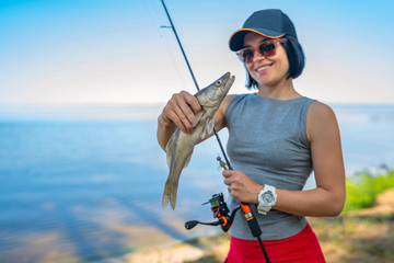 Happy fisher girl with walleye zander fish trophy at lake shore