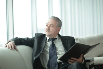 boss with clipboard sitting on the office couch.business concept