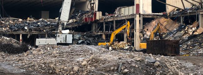 Demolition team machines demolishing a big factory
