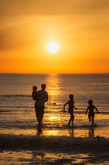 Family resting on the sea. Children play in the sea at sunset.