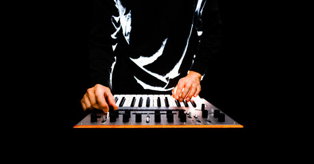 male musician playing music keyboard synthesizer on black background