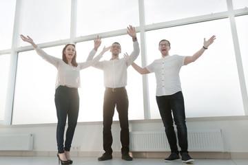 happy business team standing near office window.