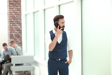 serious businessman talking on mobile phone in office