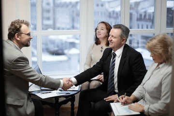 friendly handshake of business partners in the office