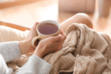 Young woman drinking hot tea at home, closeup