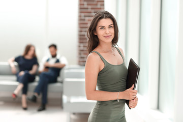 young business woman with clipboard standing in office lobby