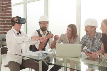 young designer uses virtual reality glasses at a meeting in the office.