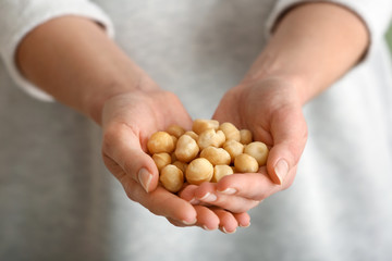 Woman holding peeled macadamia nuts, closeup