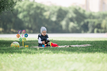 little boy playing with toys sitting on the lawn in the Park