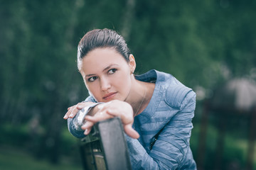 attractive young woman sitting on a Park bench