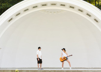 Woman playing guitar, man jumping next to her