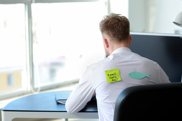 Sticky note with text APRIL FOOL'S DAY and paper fish on back of man working in office Wall mural
