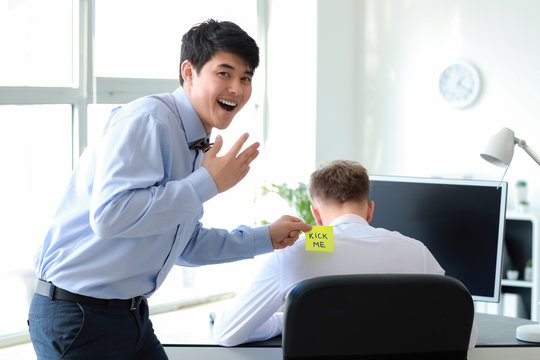 Asian man playing a prank on his colleague in office. April Fools' Day prank