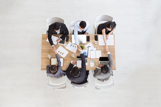 Top view of businessmen shaking hands sitting at conference table during team meeting, Entrepreneurs handshaking making deal starting collaboration at group negotiations teamwork with blank copy space