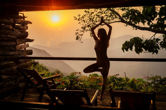 woman in tropical open yoga studio place a view outside to the hills while sunset.girl in eco hotel panoramic windows enjoying solitude with nature Kerala India wildernest resort