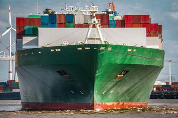 Frontal-Aufnahme eines grünen Containerschiffes