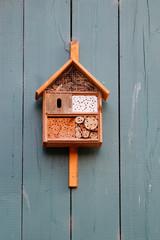 Insektenhotel in einem orange farbenen Haus an einer Holzwand